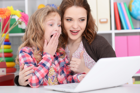 mother and daughter using laptop 스톡 콘텐츠