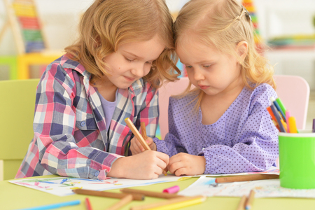 Cute little girls drawing with pencils