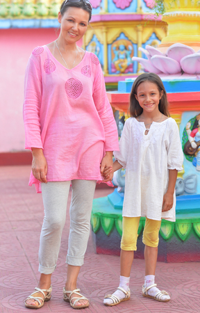 Portrait of mother and daughter posing on blurred amusement park background