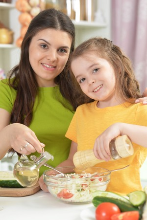 Cute little girl with her mother cooking together