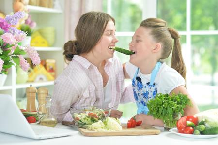 Two girls having fun while preparing fresh salad