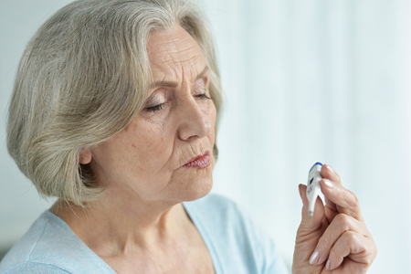 Portrait of old sick woman with thermometer