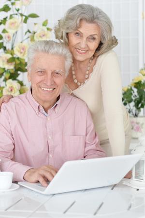 Happy senior couple portrait drinking tea and using laptop