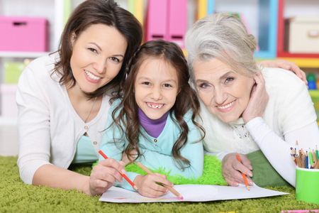 Grandmother and mother reading book with little girl 스톡 콘텐츠