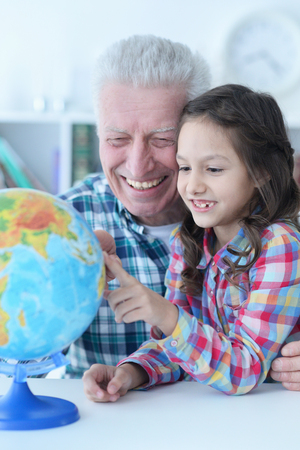 Portrait of grandfather and granddaughter exploring world globe 스톡 콘텐츠