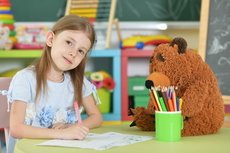 Cute schoolgirl sitting and drawing