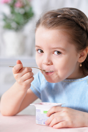 Portrait of cute little girl eating delicious yogurt