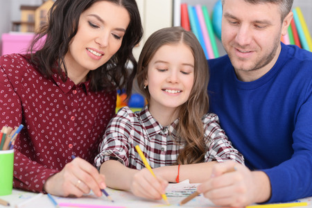 Portrait of parents and daughter drawing together in room