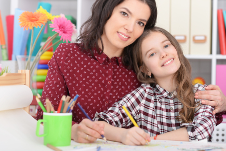 Mother and daughter drawing together  in room 스톡 콘텐츠