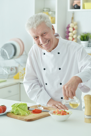 Portrait of elderly male chef pouring oil into salad