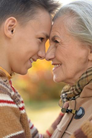 Portrait of grandmother and grandson hugging in park