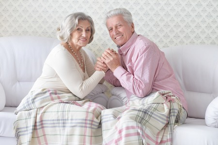 Portrait of happy senior couple resting and posing at home