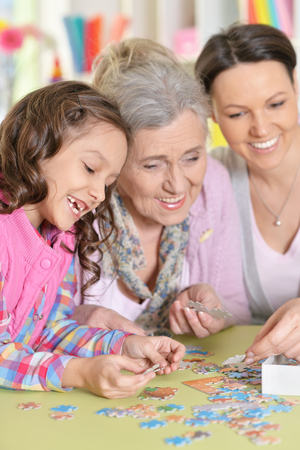 Grandmother with daughter and little granddaughter collecting puzzle