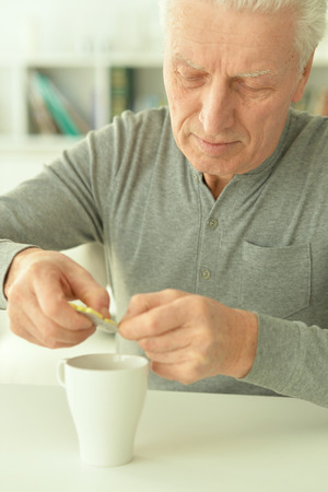Elderly ill man with pills in hand