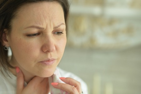 Portrait of sick young woman with sore throat Stock Photo