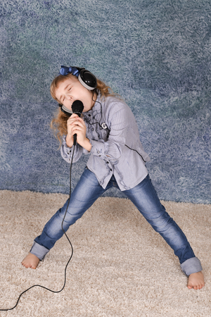 Beautiful little girl with microphone at home singing Imagens