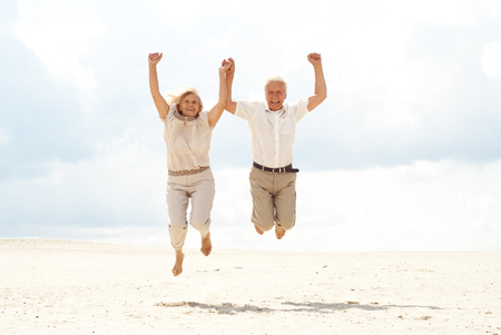 Superb elderly couple enjoy the sea breeze