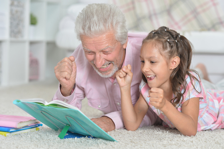 Portrait of grandfather reading book with his little granddaughter 写真素材