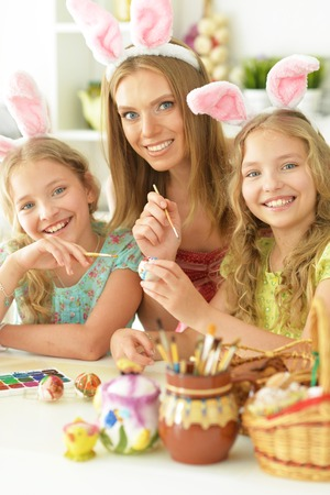 Mother with daughters wearing rabbit ears decorating Easter eggs Stock Photo - 118907628
