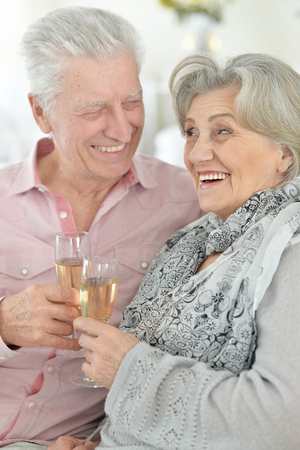 Portrait of mature couple drinking champagne at home, close up