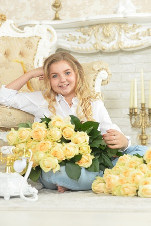 Cute curly teen girl posing with bouquet of yellow roses Фото со стока