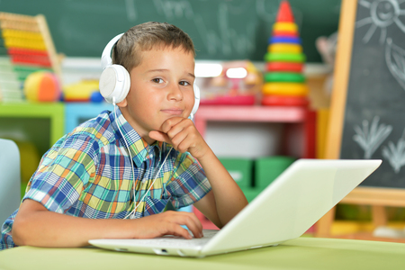 Portrait of little boy with headphones using laptop in classroom