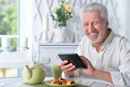 happy senior man using tablet while drinking tea at kitchen