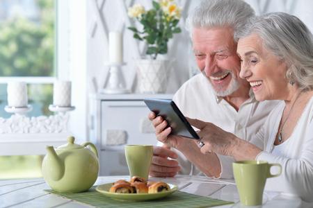 senior couple using tablet while drinking tea