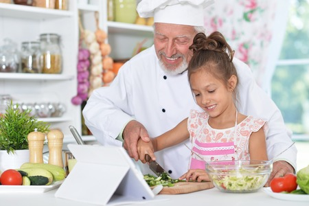man preparing dinner with granddaughter