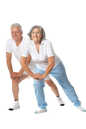 Cute senior couple exercising on white background 免版税图像