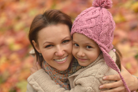 Portrait of cute mother with daughter in autumn park Banco de Imagens