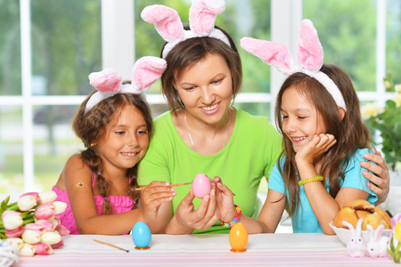 Portrait of mother and daughters coloring Easter eggs 스톡 콘텐츠