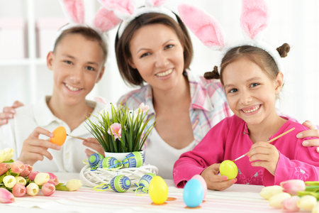 Portrait of family painting traditional Easter eggs in different colors at home