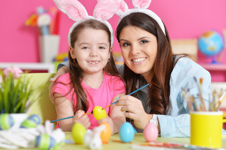 Portrait of mother and daughter decorating Easter eggs