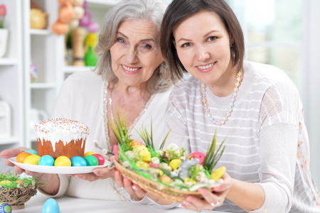 Close-up portrait of mother and daughter colouring eggs Archivio Fotografico