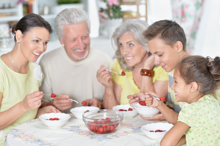 Portrait of big happy family eating fresh strawberries at kitchen Stock Photo