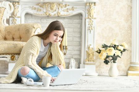 Beautiful teen girl sitting on floor and using laptop