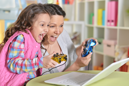 portrait of happy mother and daughter playing game