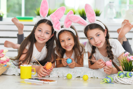 Cute girls wearing rabbit ears decorating Easter eggs Stock Photo - 119245017