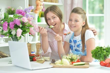 Portrait of funny girls preparing fresh salad