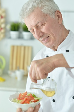 Close-up portrait of elderly male chef pouring oil into salad