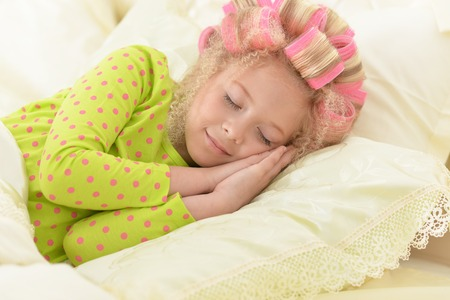 Lovely little girl with pink curlers sleeping