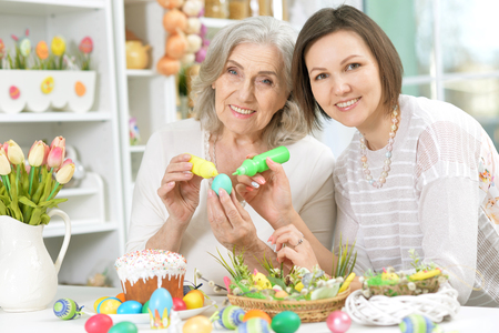 Portrait of mother and daughter colouring eggs Stock Photo