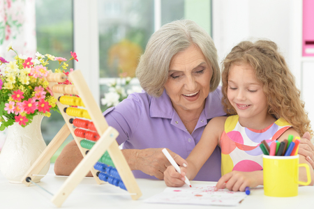 Portrait of cute curly schoolgirl studying with grandmother in her room