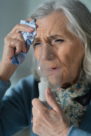 Portrait of senior woman with inhaler Foto de archivo