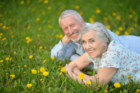 Senior couple lying on green meadow with dandelions