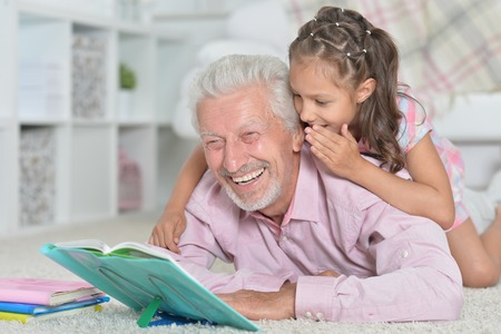 Grandfather reading book with his granddaughter Banco de Imagens