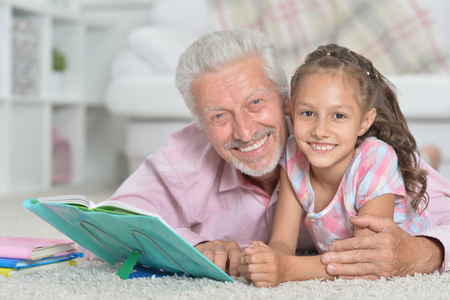Grandfather reading book with his little granddaughter