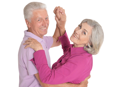 Portrait of happy senior couple dancing on white background