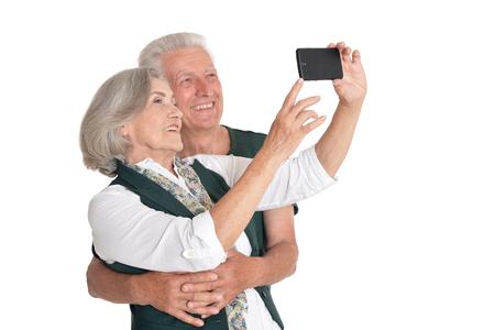 Portrait of senior couple taking selfie on white background